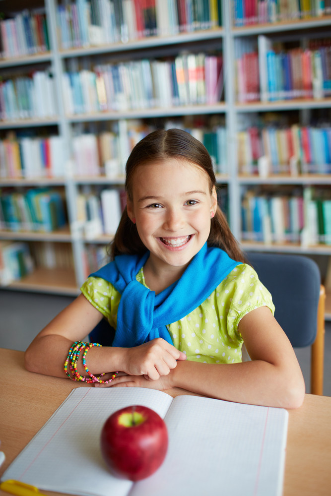 Portrait Of Happy Schoolgirl Sitting And Looking At Camera In Library