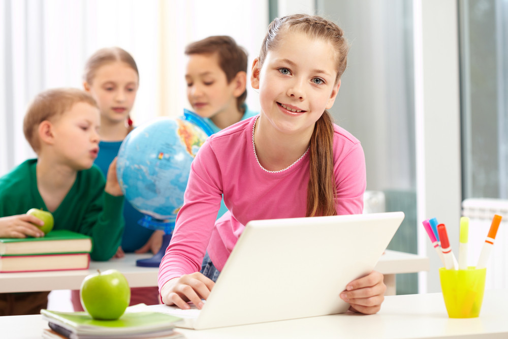 Portrait Of Smart Schoolgirl Sitting In Classroom With Her Classmates On Background