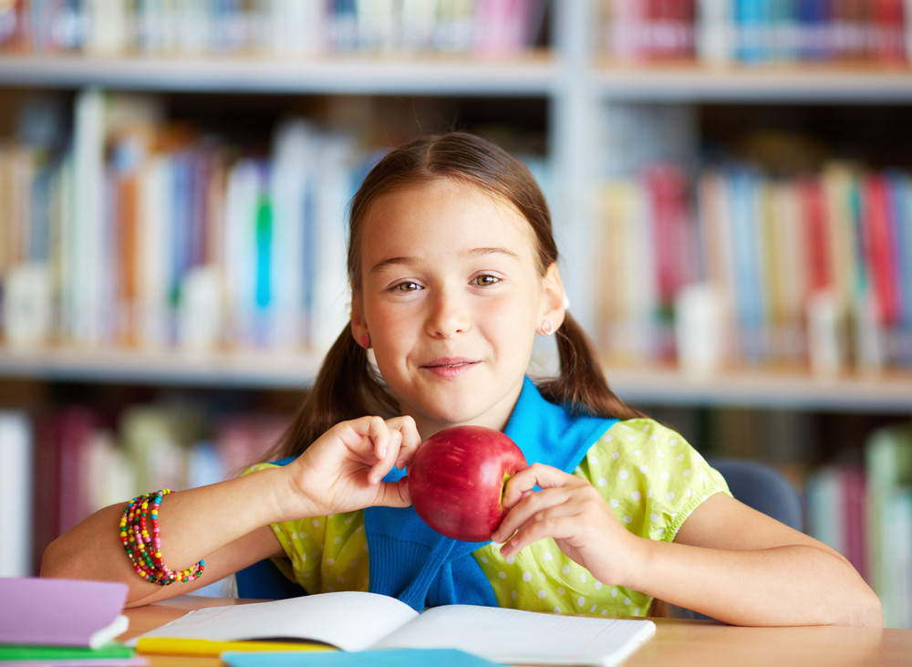 Portrait Of Happy Schoolgirl With Apple Looking At Camera In Library