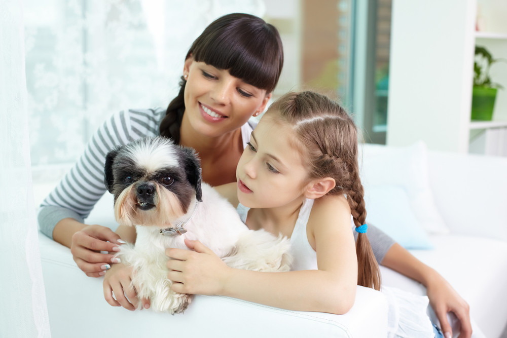 Portrait Of Happy Girl Holding Pet And Looking At It With Her Mother Near By