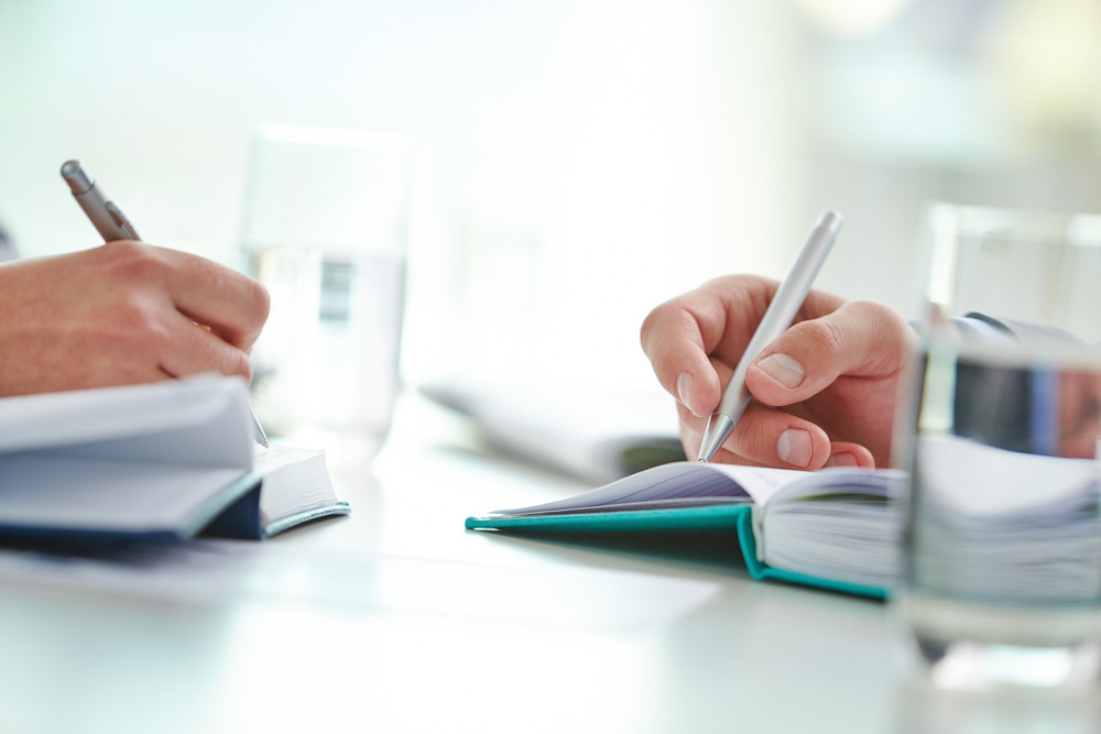 Male And Female Hands With Pens Writing Something In Notebooks