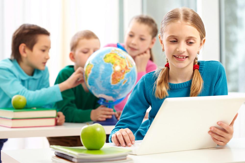 Portrait Of Smart Schoolgirl Working With Laptop On Background Of Her Classmates