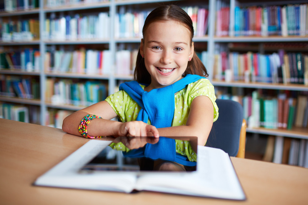 Portrait Of Cheerful Schoolgirl Looking At Camera While Sitting In Library