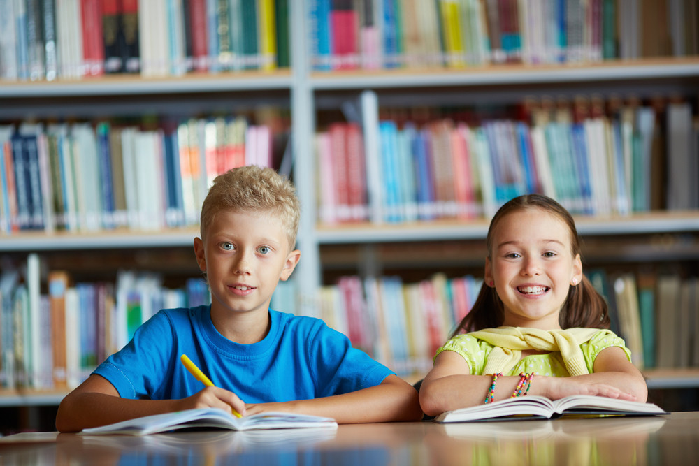 Portrait Of Cheerful Schoolchildren Looking At Camera While Sitting In Library