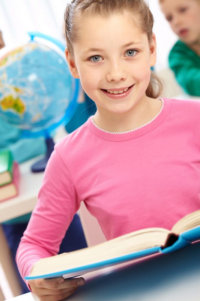 Portrait Of Smart Schoolgirl With Open Book Looking At Camera