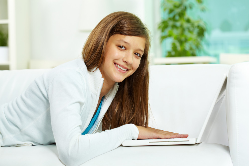 Cute Girl With Laptop Looking At Camera