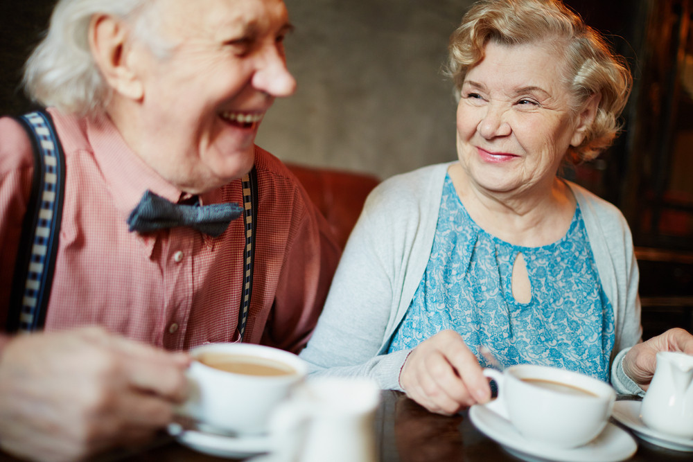 Portrait Of Retired Couple In Smart Clothes Having Tea In Cafe