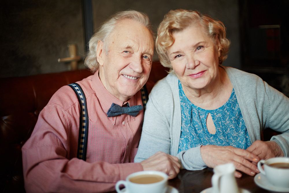 Portrait Of Retired Couple In Smart Clothes Looking At Camera In Cafe