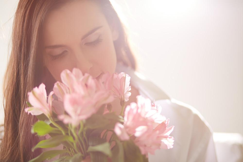 Portrait der schönen Dame Blick in die Blumen und Riechen Them