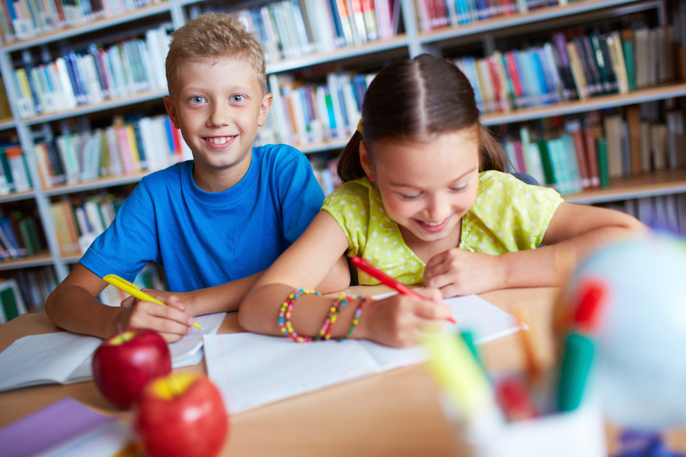 Portrait Of Two Schoolkids Sitting In Library And Making Notes