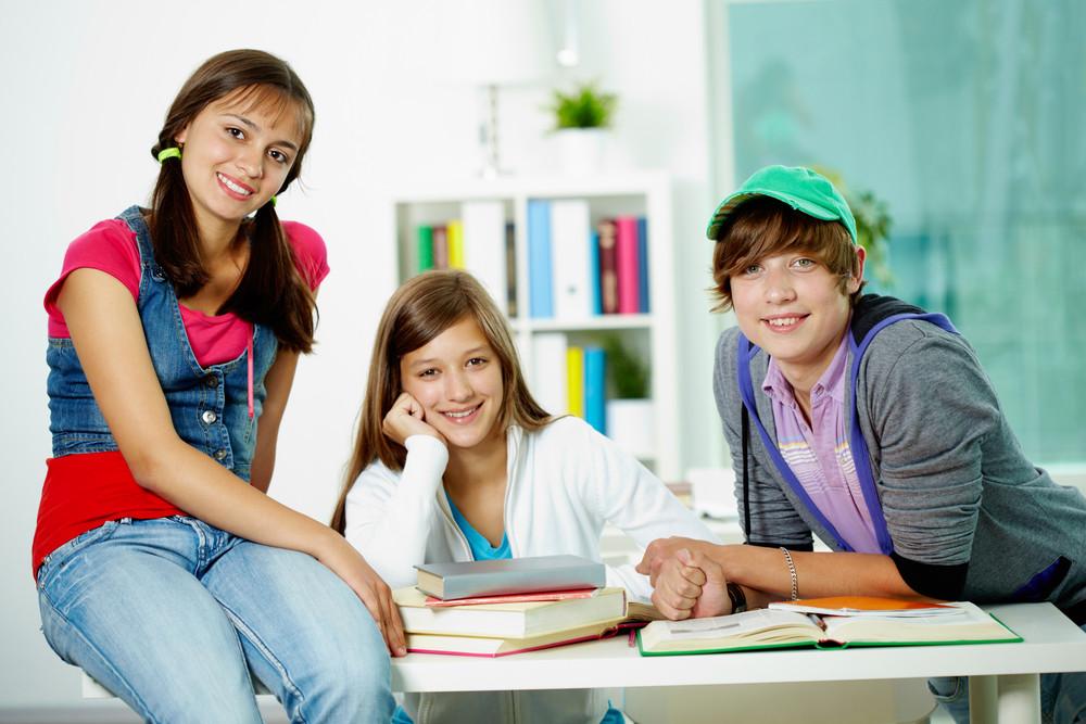 Portrait Of Three Smart Classmates Looking At Camera In Classroom