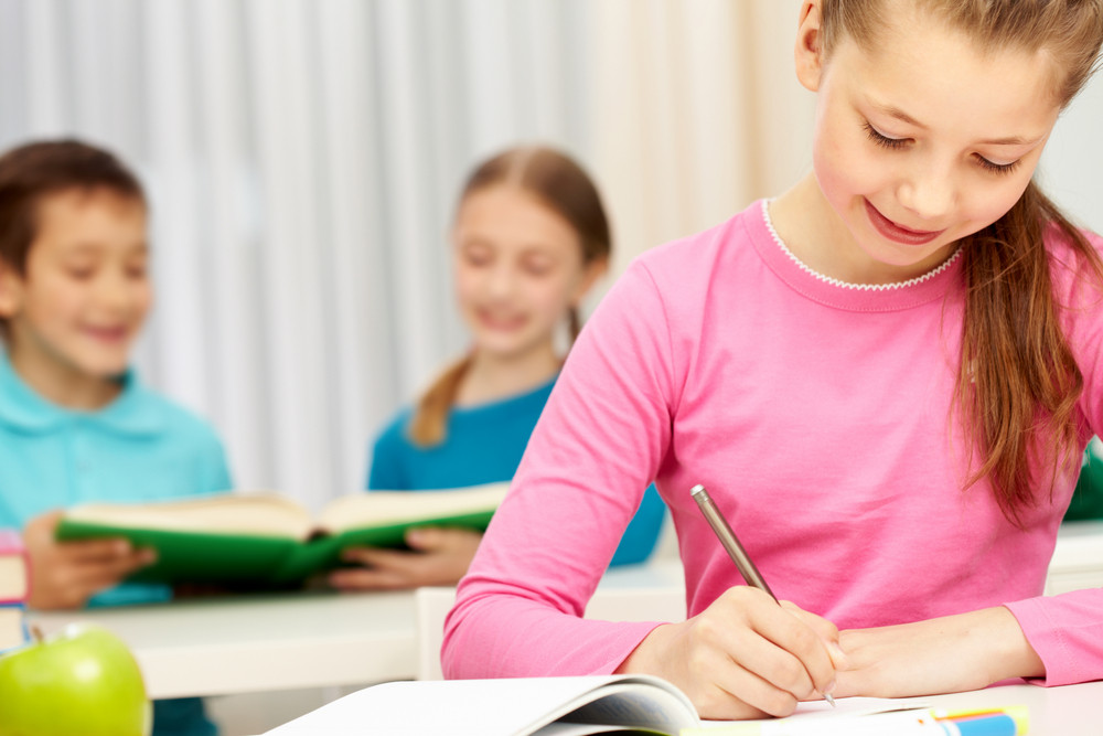 Portrait Of Smart Schoolgirl Making Notes In Her Exercise Book