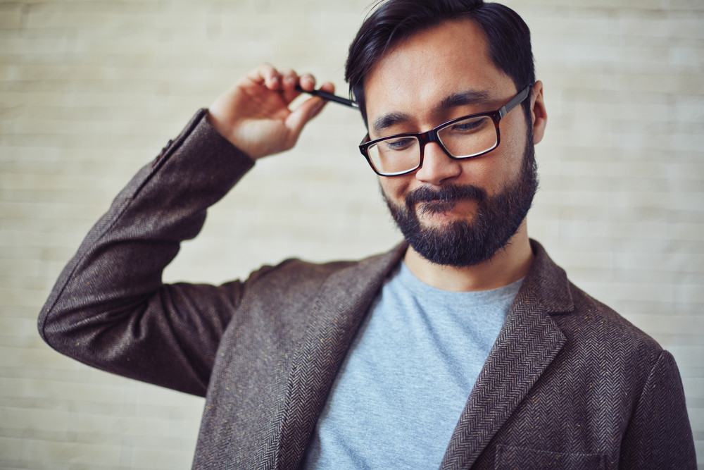 Handsome Businessman In Eyeglasses Doubting About Something
