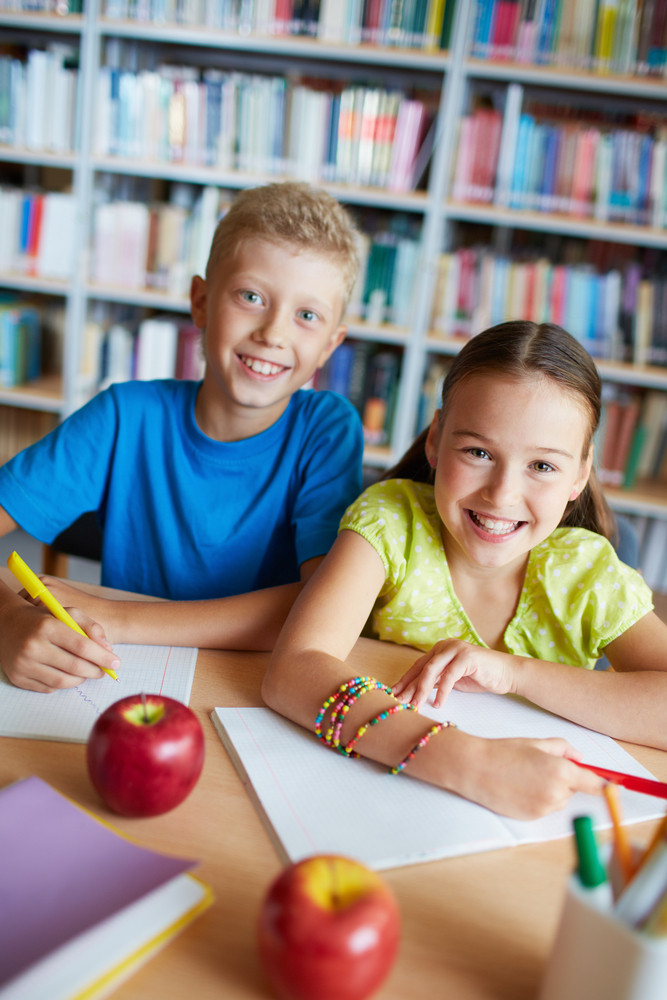 Portrait Of Happy Schoolkids Looking At Camera While Sitting In Library