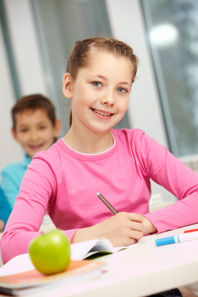 Portrait Of Smart Schoolgirl Making Notes And Looking At Camera