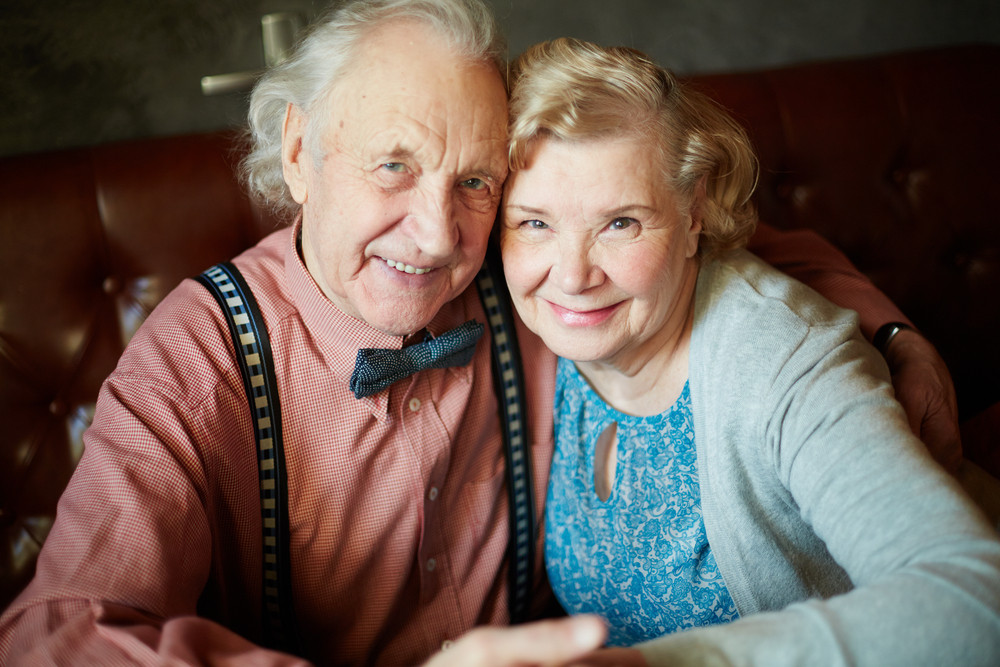 Portrait Of Retired Couple In Smart Clothes Looking At Camera