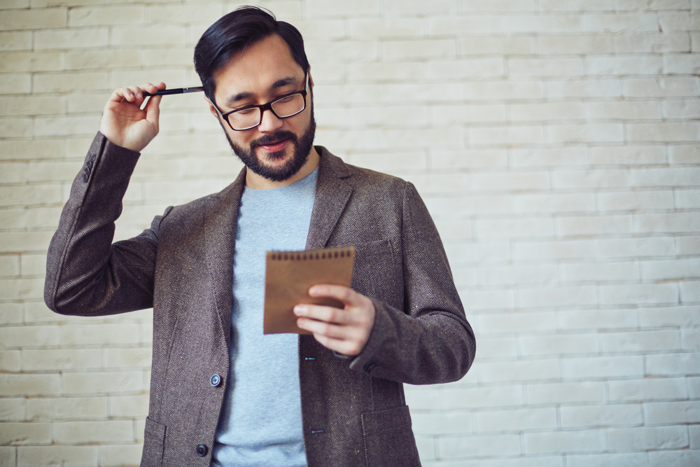 Male Employee In Eyeglasses Looking At Page Of Notepad