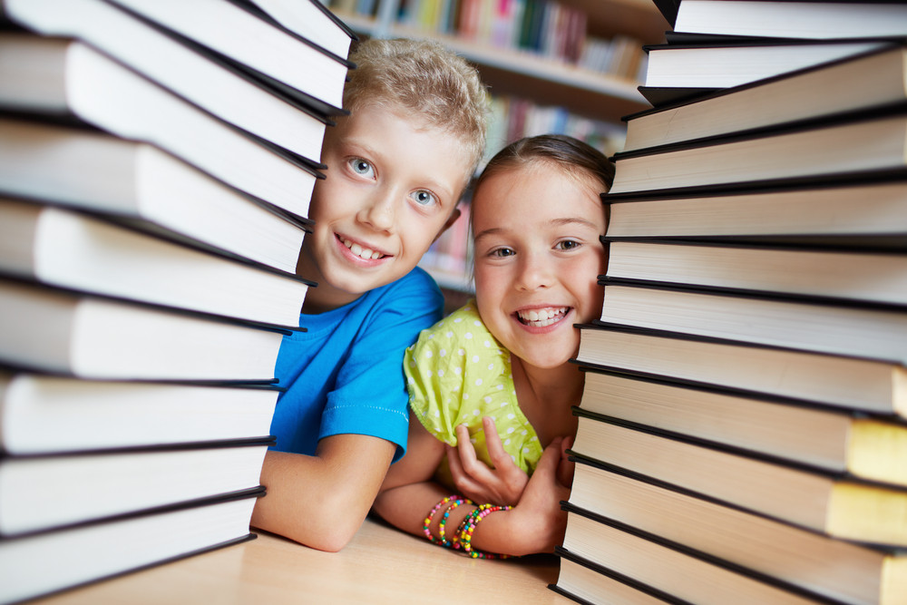 Portrait Of Happy Schoolkids Between Stacks Of Books Looking At Camera