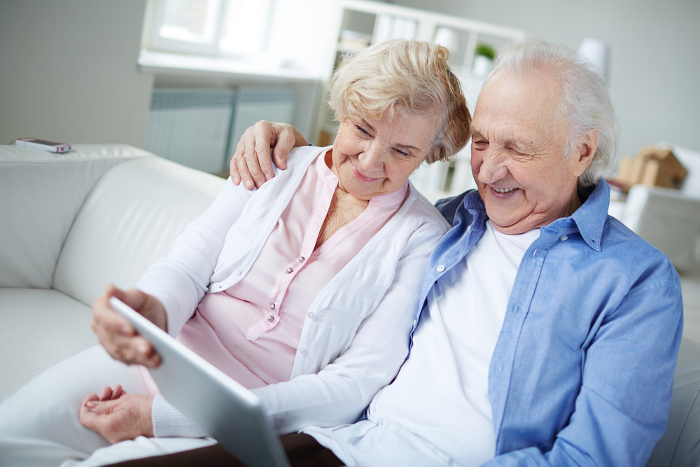 Senior Couple With Touchpad Sitting At Home And Networking