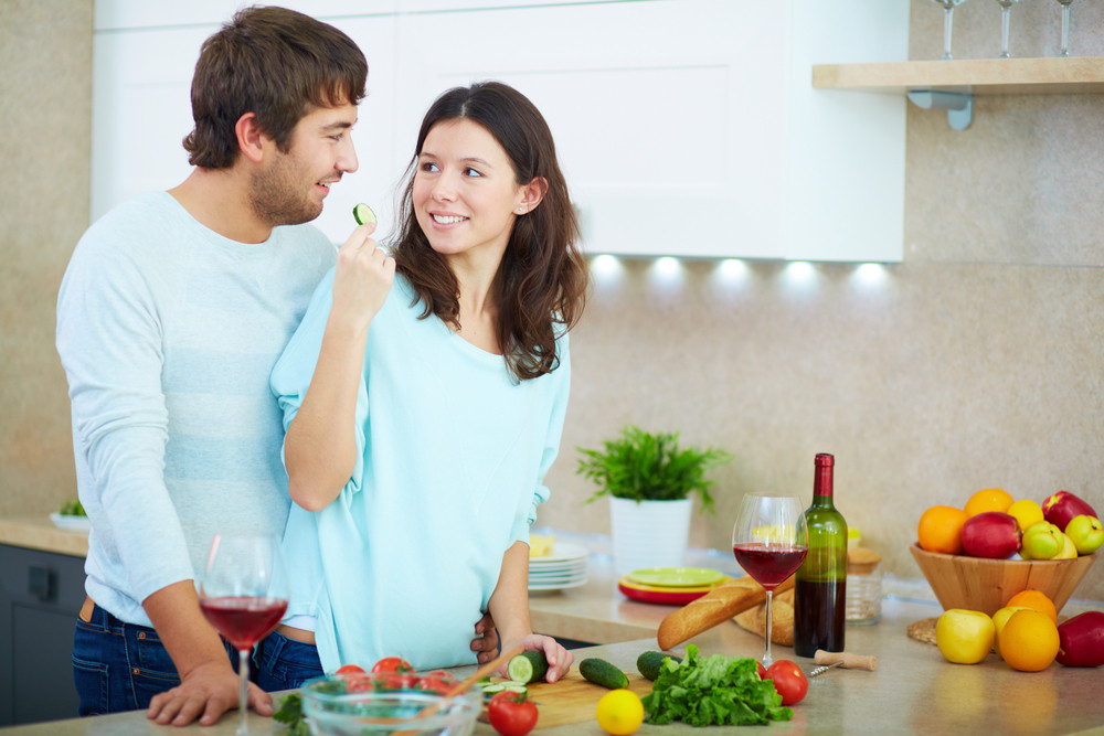 Portrait Of Young Man And His Wife Cooking Vegetable Salad In The Kitchen