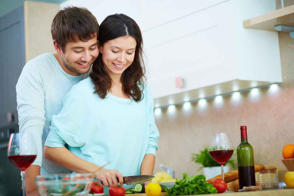 Portrait Of Young Woman Cooking Salad With Her Husband Near By