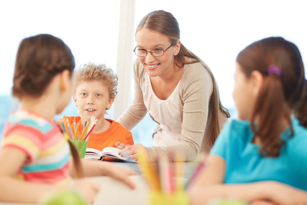 Portrait Of Pretty Teacher Interacting With Pupils At Reading Lesson