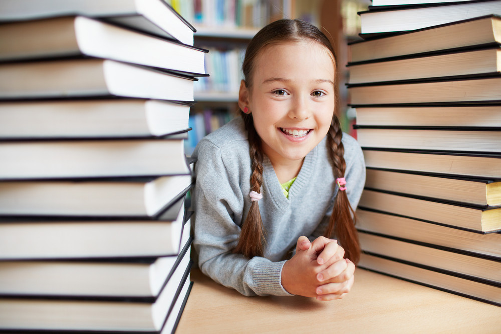 Portrait Of Happy Schoolkid Looking At Camera Surrounded By Two Stacks Of Books