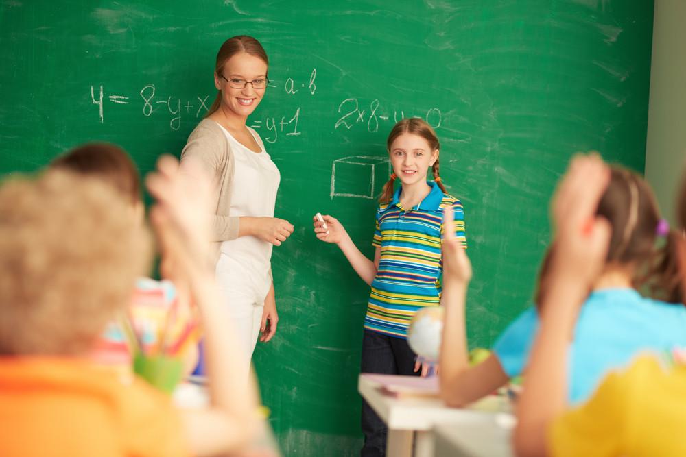 Portrait Of Smart Teacher And Schoolgirl Standing By Blackboard And Looking At Schoolkids In Classroom