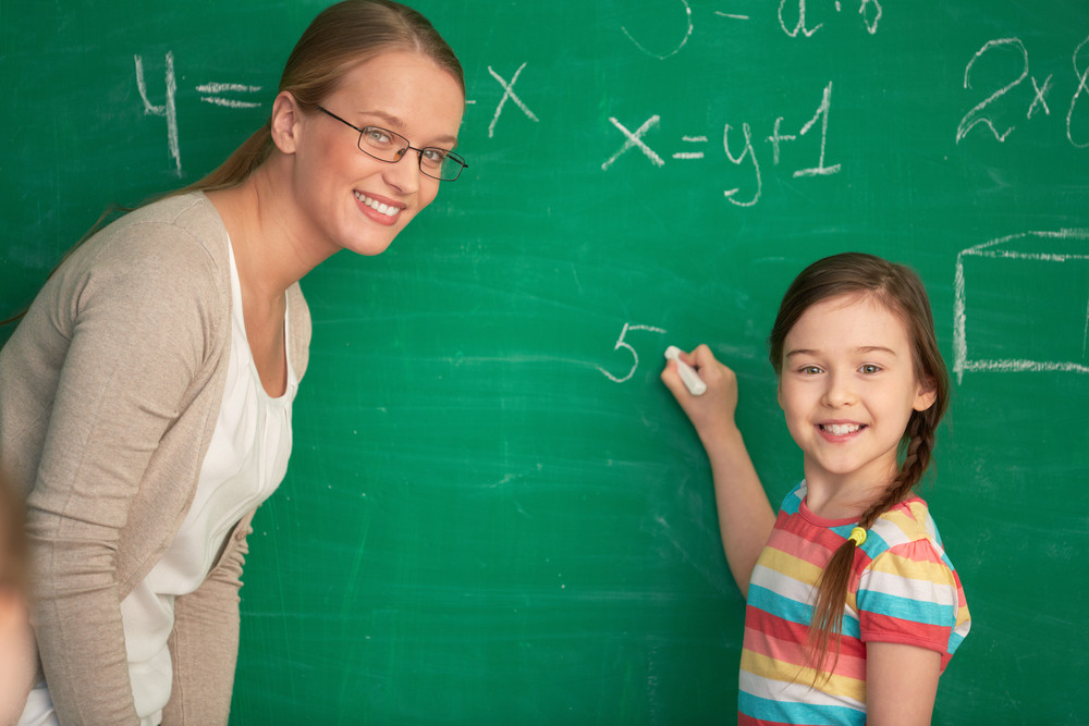 Portrait Of Smart Teacher And Schoolgirl Standing By Blackboard And Looking At Camera