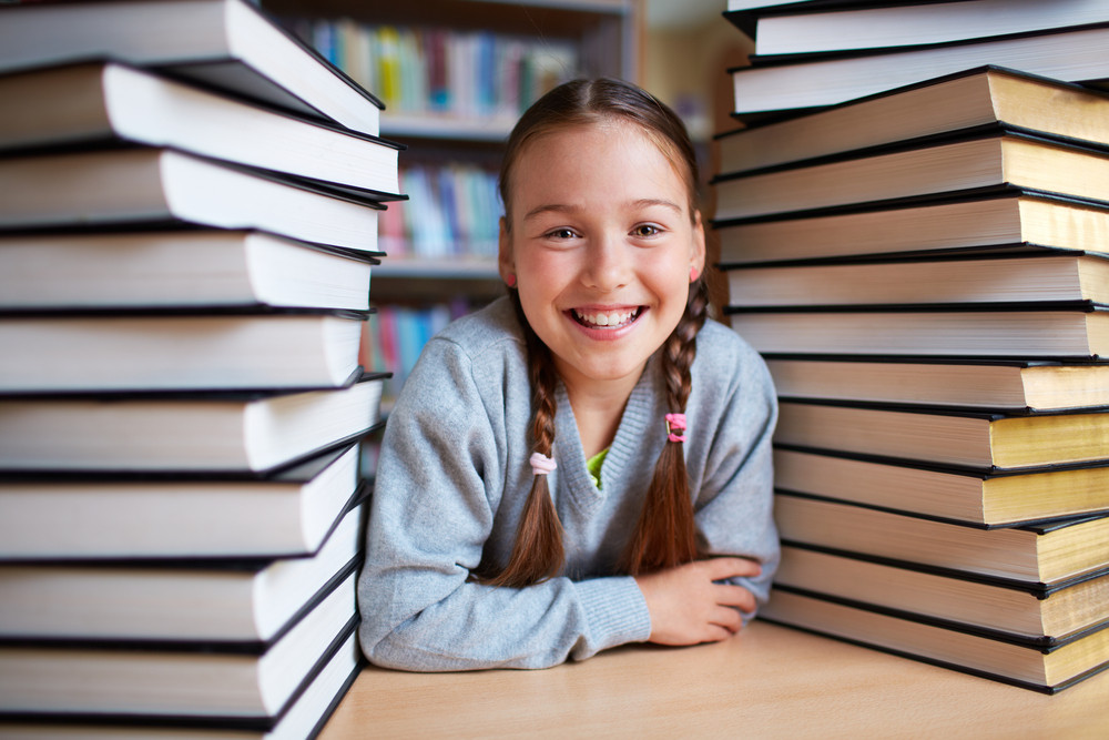 Portrait Of Happy Schoolgirl Looking At Camera Surrounded By Two Stacks Of Books