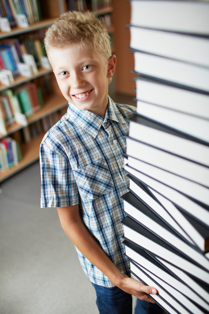 Portrait Of Happy Schoolkid Looking At Camera While Holding Huge Stack Of Books