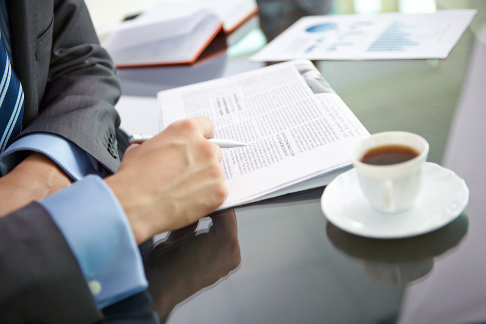 Male Hand With Pen Over Newspaper And Cup Of Coffee Near By