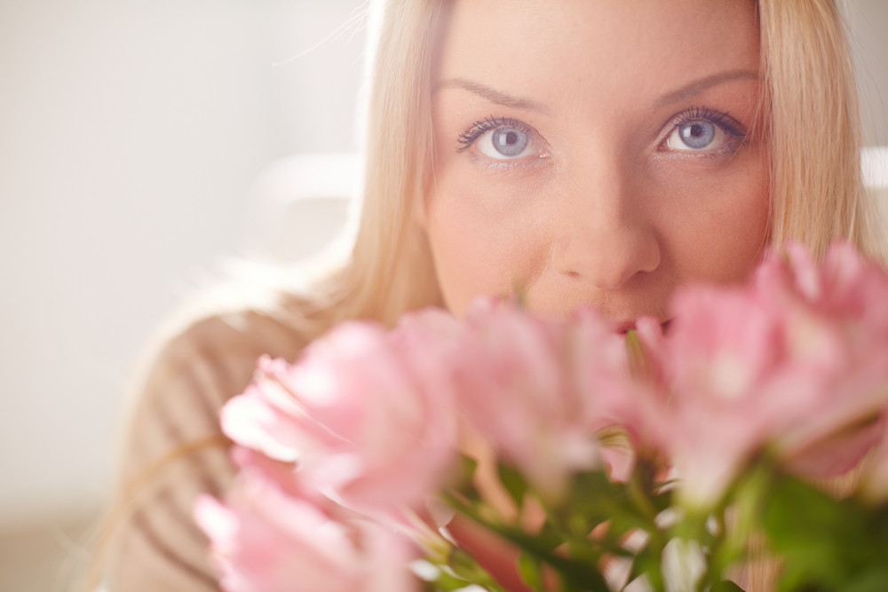 Portrait Of Lovely Lady Looking At Camera While Smelling Pink Flowers