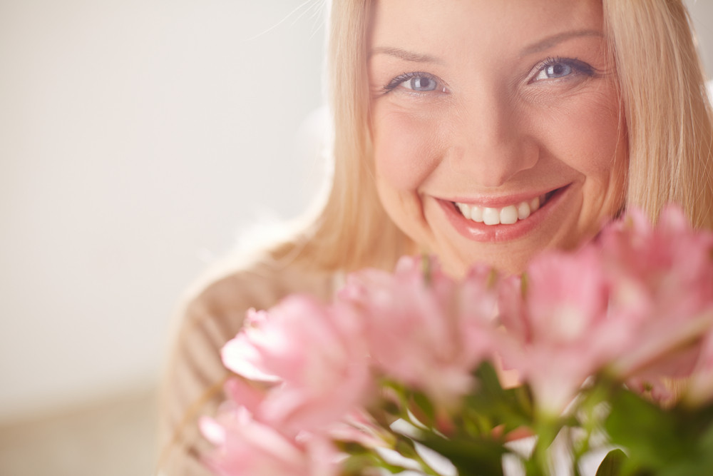 Portrait Of Lovely Lady Looking At Camera With Bunch Of Pink Flowers