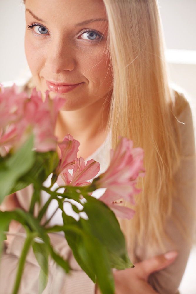 Portrait Of Lovely Lady Looking At Camera With Bunch Of Pink Flowers Near By