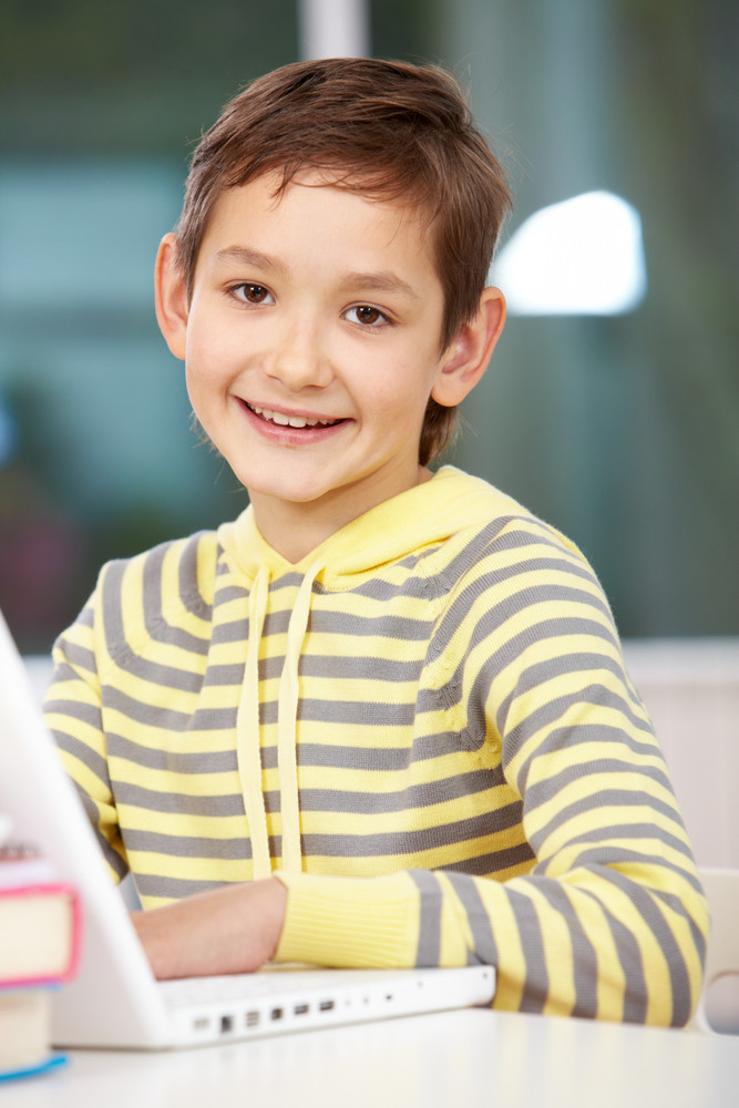 Portrait Of Smart Schoolboy Looking At Camera While Typing On Laptop