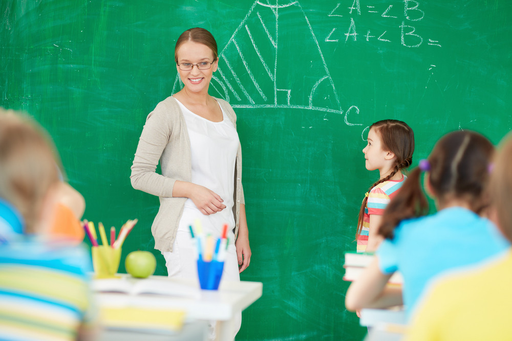 Portrait Of Smart Teacher Standing By Blackboard And Looking At Schoolkids While One Of Pupils Standing By Her
