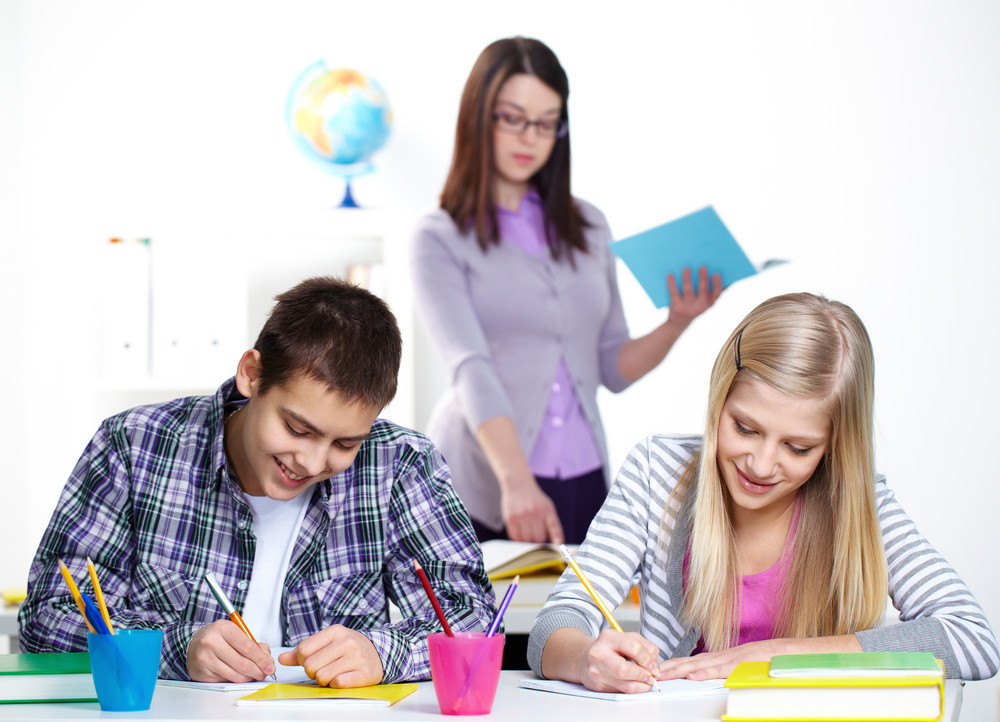 Portrait Of Happy Lad And Girl Writing Somethinig During Lesson