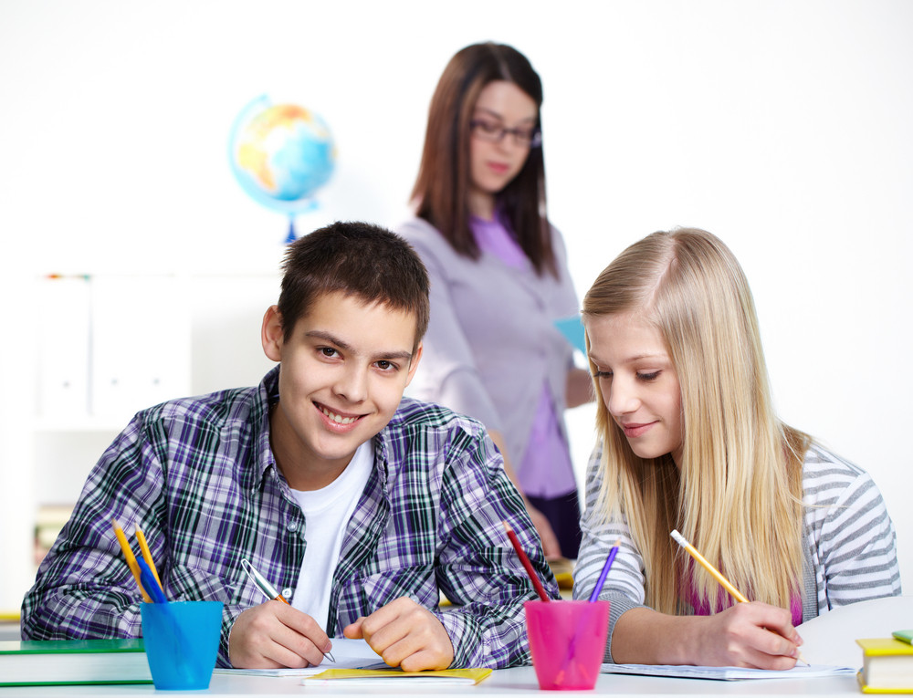 Portrait Of Happy Lad And Girl Sitting At Lesson