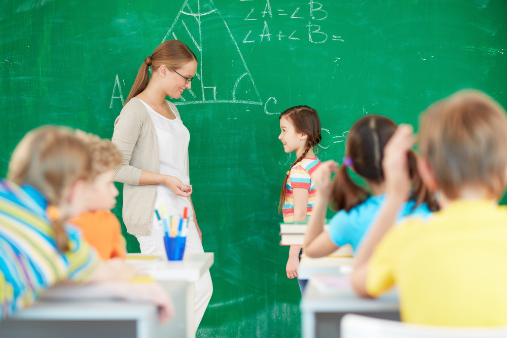 Portrait Of Smart Teacher Standing By Blackboard And Looking At One Of Pupils Standing Near By