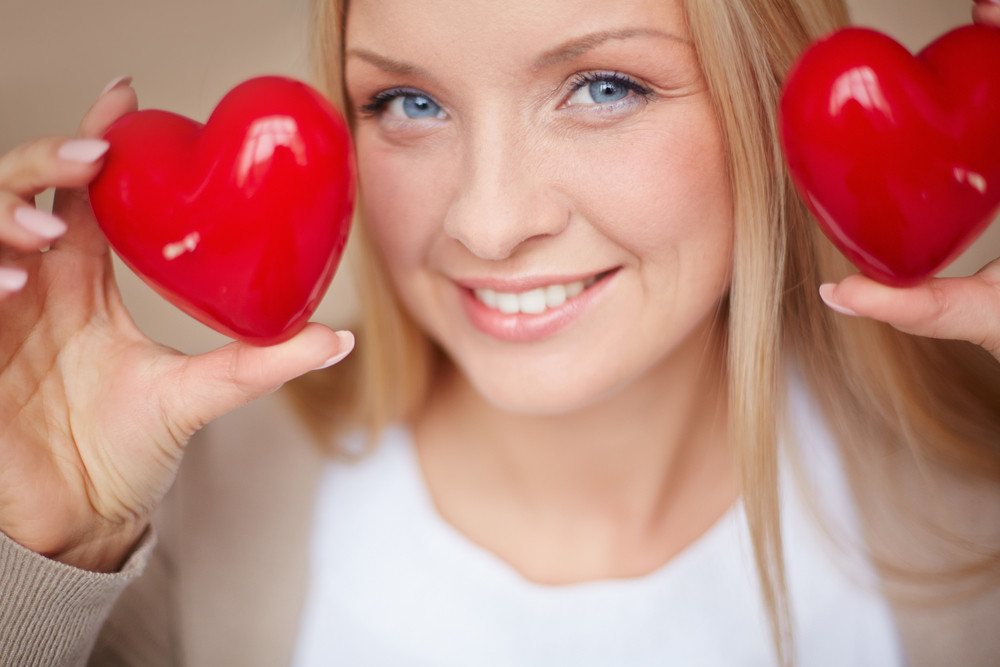Image Of Smiling Female With Two Red Hearts In Hands Looking At Camera