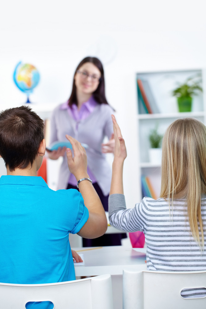 Back View Of Clever Teenagers Raising Arms To Answer During Lesson