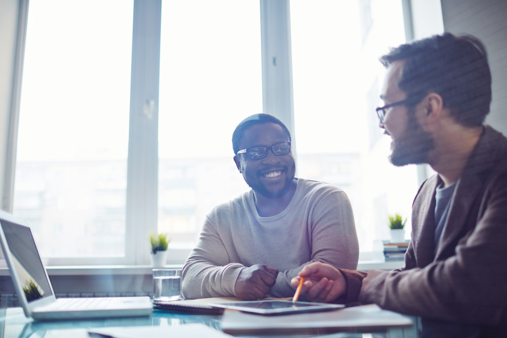 Asian And African Employees Discussing Ideas In Office