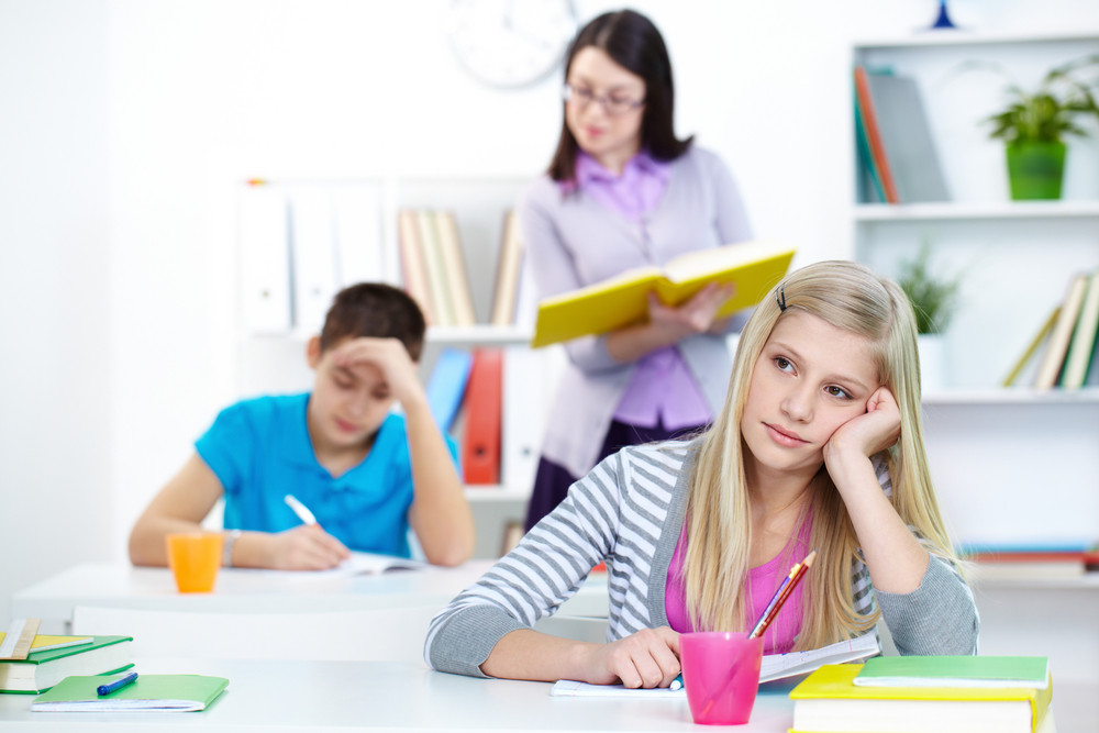 Portrait Of Bored Teenage Blonde Sitting At Lesson With Teacher And Classmate On Background