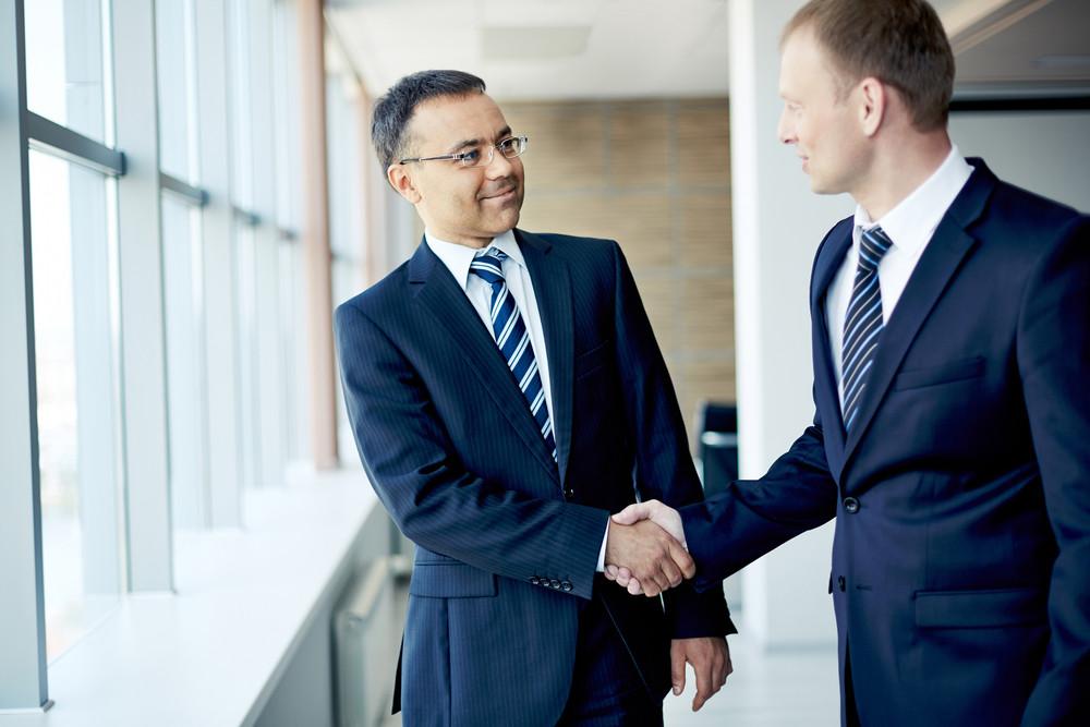 Portrait Of Elegant Businessmen Handshaking In Conference Hall