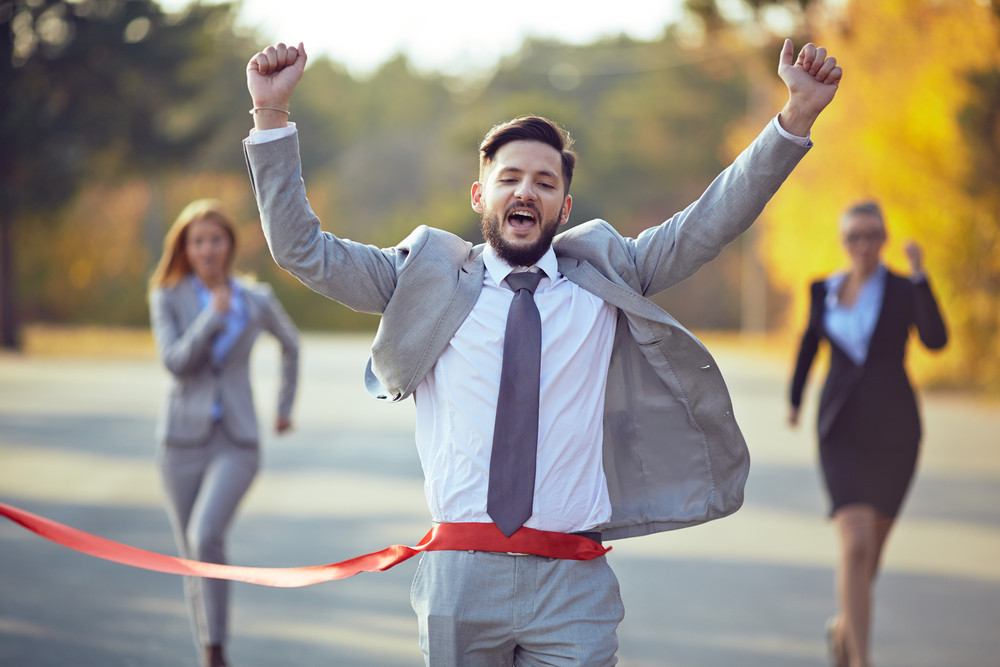 Winning Businessman Coming To Finish With Two Female Colleagues On Background