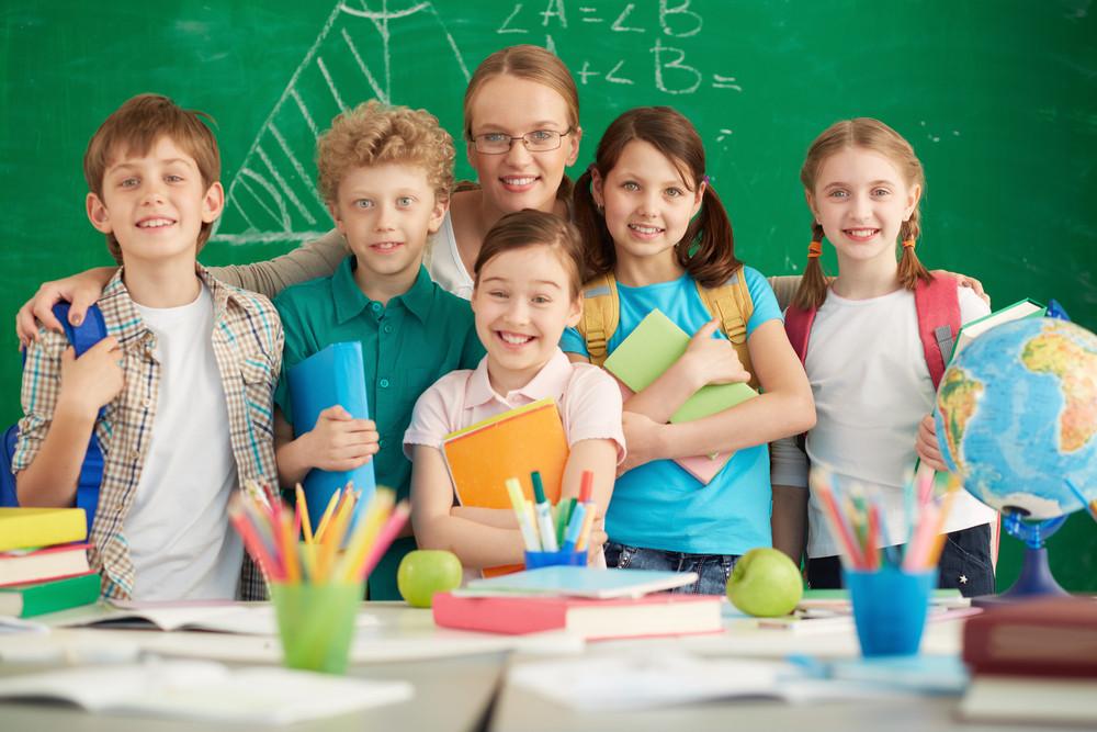 Portrait Of Cute Schoolchildren And Their Teacher On Background Of Blackboard