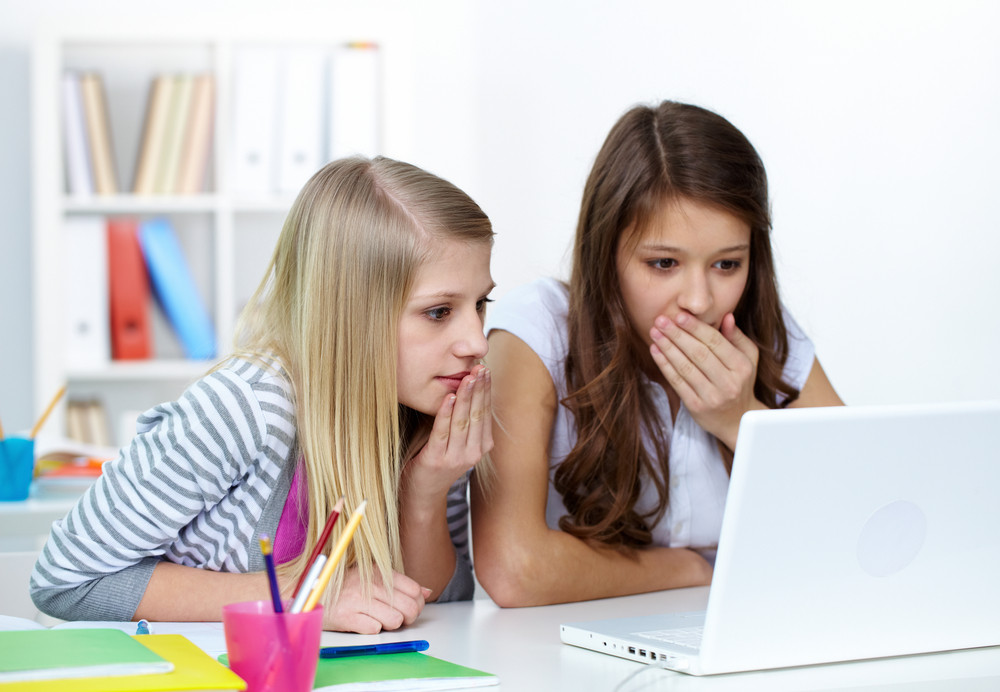 Two Astounded Girls Looking At Laptop Screen In College