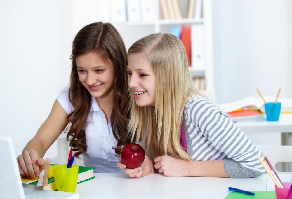 Cute Girls Looking At Something Interesting In Laptop During Break In College