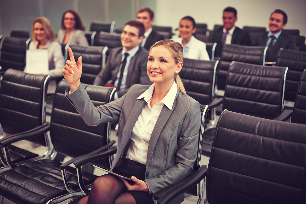 Image Of Business People Sitting In Rows At Seminar With Pretty Woman In Front Raising Her Arm